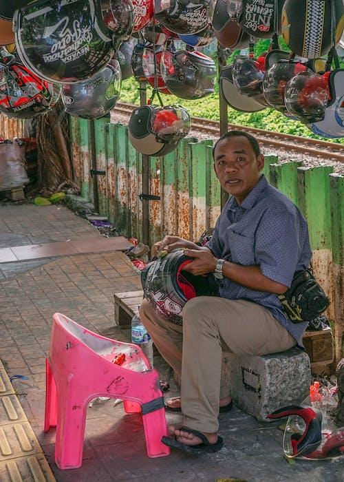 Man in Blue Polo Selling Helmets on Sidewalk