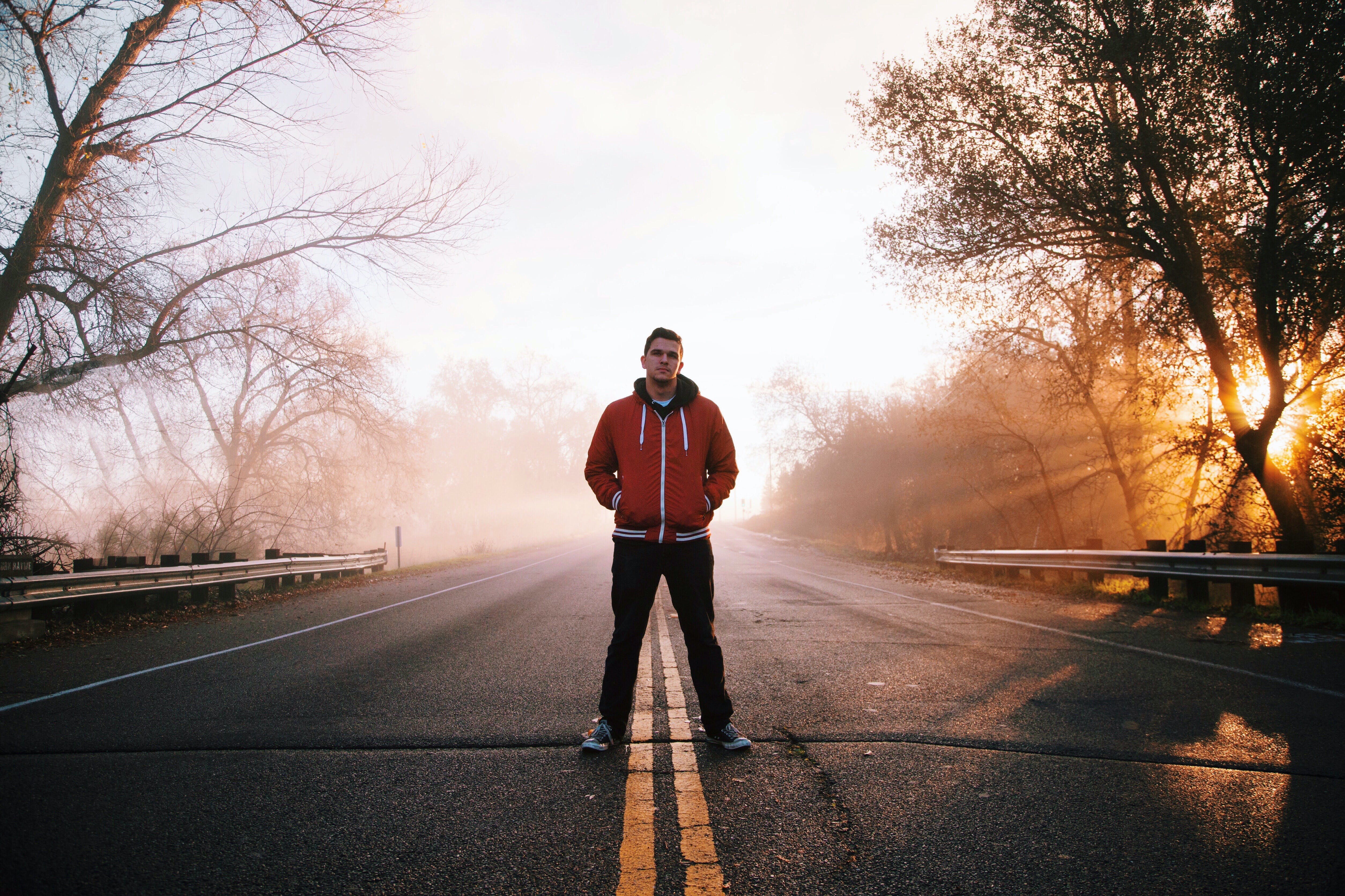 Man Standing on Gray Concrete Top Road Wearing Red and Black Zip-up Hooded Jacket