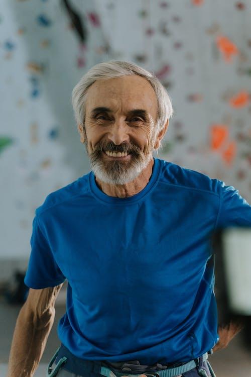 Man Wearing Blue Shirt and a Climbing Harness