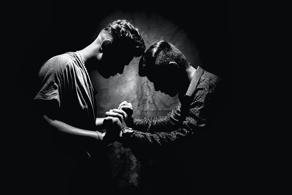 Grayscale Photo of Two Men Holding Hands