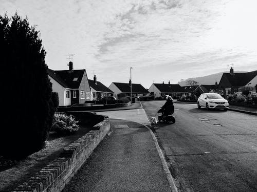 Grayscale Photo of Car Parked Beside House