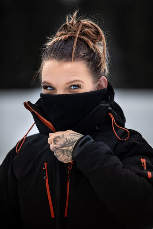 Female wearing warm jacket while covering half face with black mask and looking at camera near snowy terrain in winter day and looking at camera