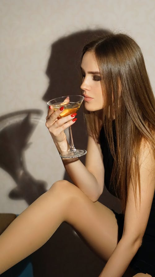 Woman in Black Tank Top Holding Clear Drinking Glass