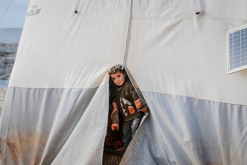 Poor ethnic boy in dirty tent