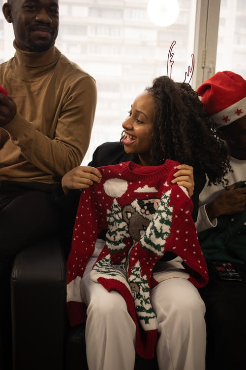 Female Happily Holding A Christmas Sweater