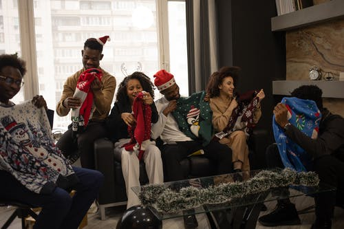 People Holding Christmas Sweaters