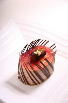 Red and Brown Oval Shape Chocolate Pastry on Ceramic Plate