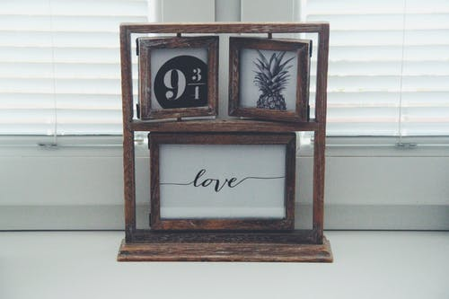 Brown Wooden Picture Frames Beside Window