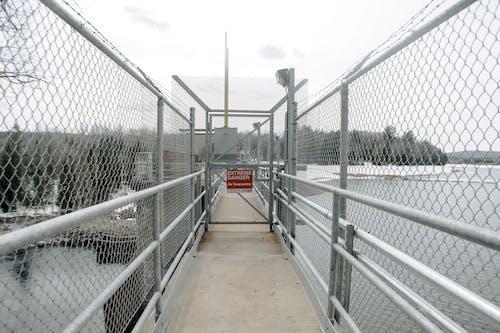 Metal fences on bridge near sea