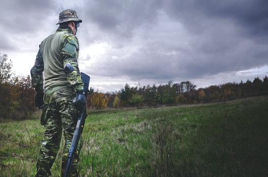 Man in Camouflage Soldier Suit While Holding Black Hunting Rifle