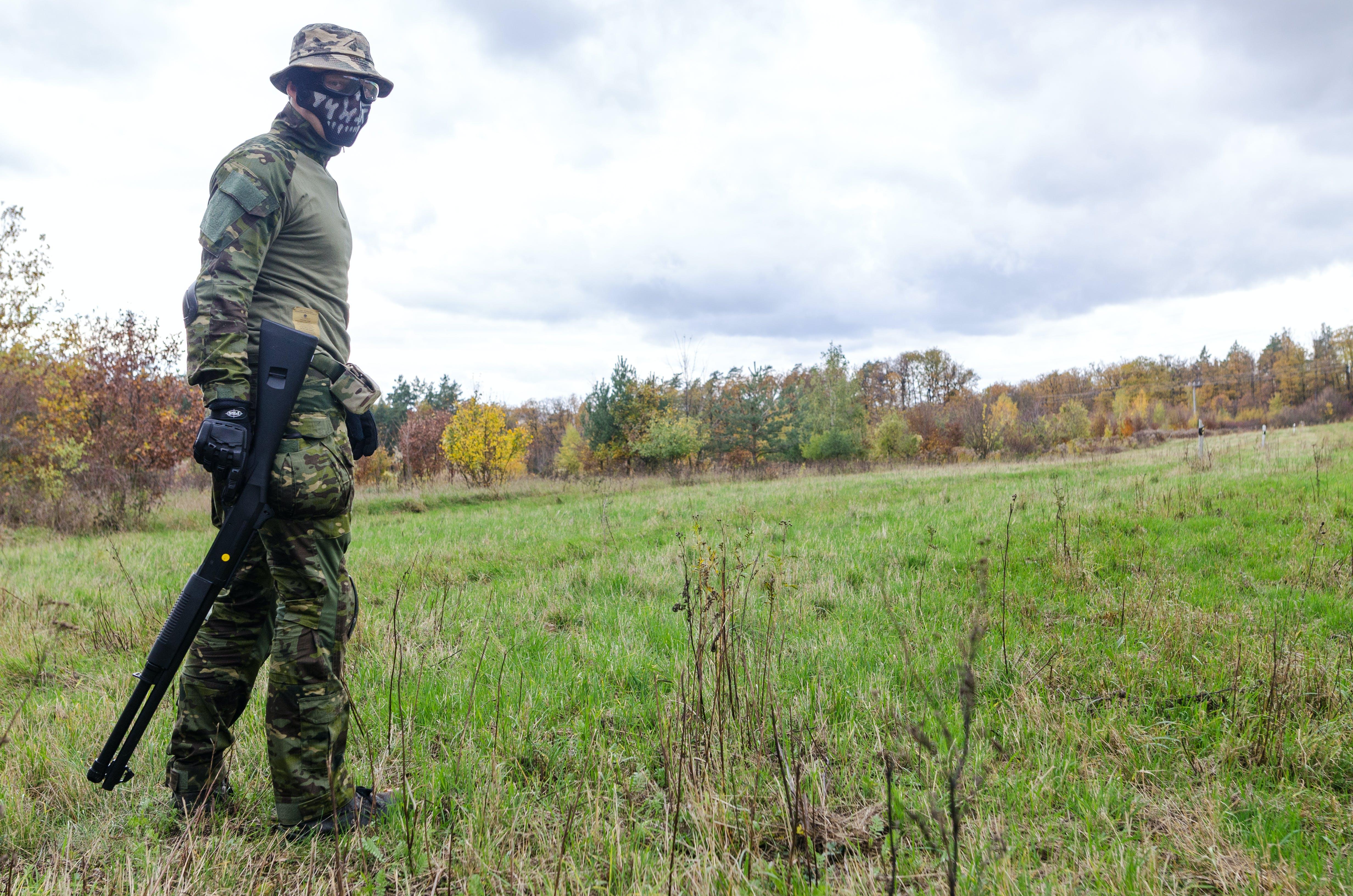 Photo of Man Wearing Green Combat Uniform Holding Rifle
