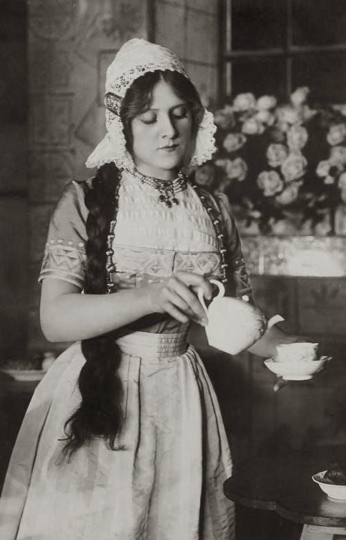 Old Photo Of Woman Pouring Tea In A Cup