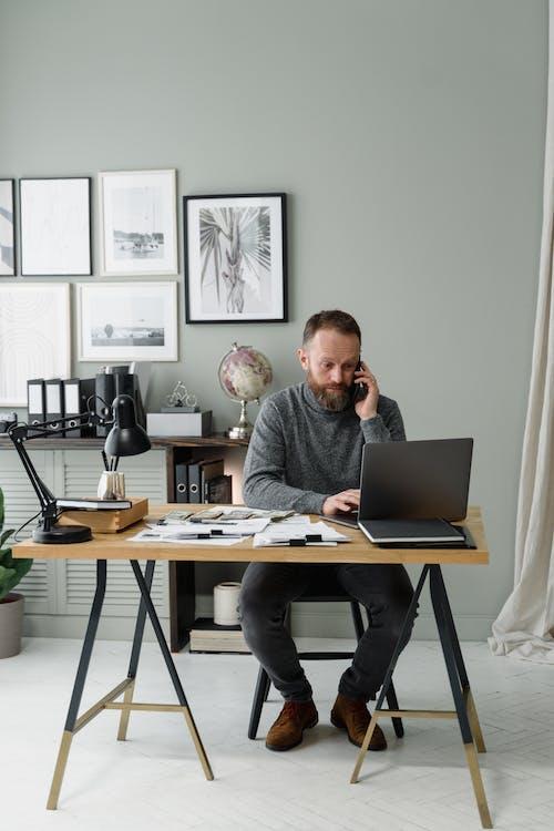 Fotos de stock gratuitas de camiseta gris, empleado de oficina, escritorio