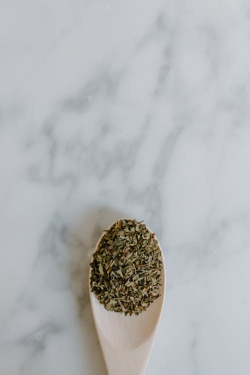 Top view of dried leaves of green tea in spoon placed on white marble surface in bright room