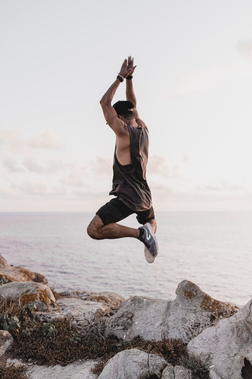 Woman in Black Tank Top and Black Shorts Jumping on Brown Rock Near Sea
