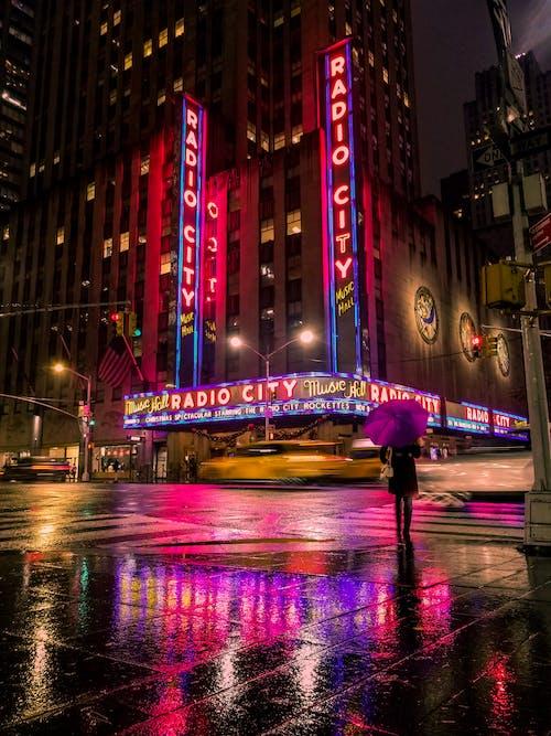 Man in Purple Shirt Walking on Sidewalk during Night Time