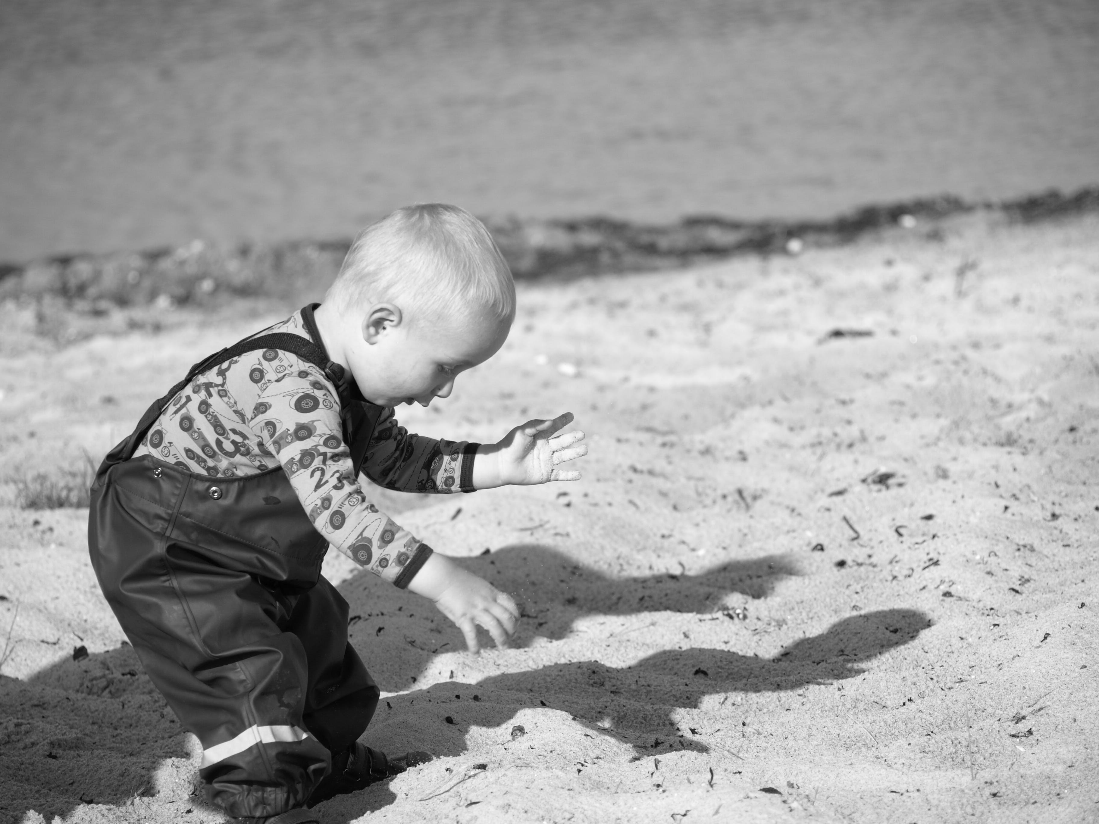 Grayscale Photography Of Toddler On Beach Sand