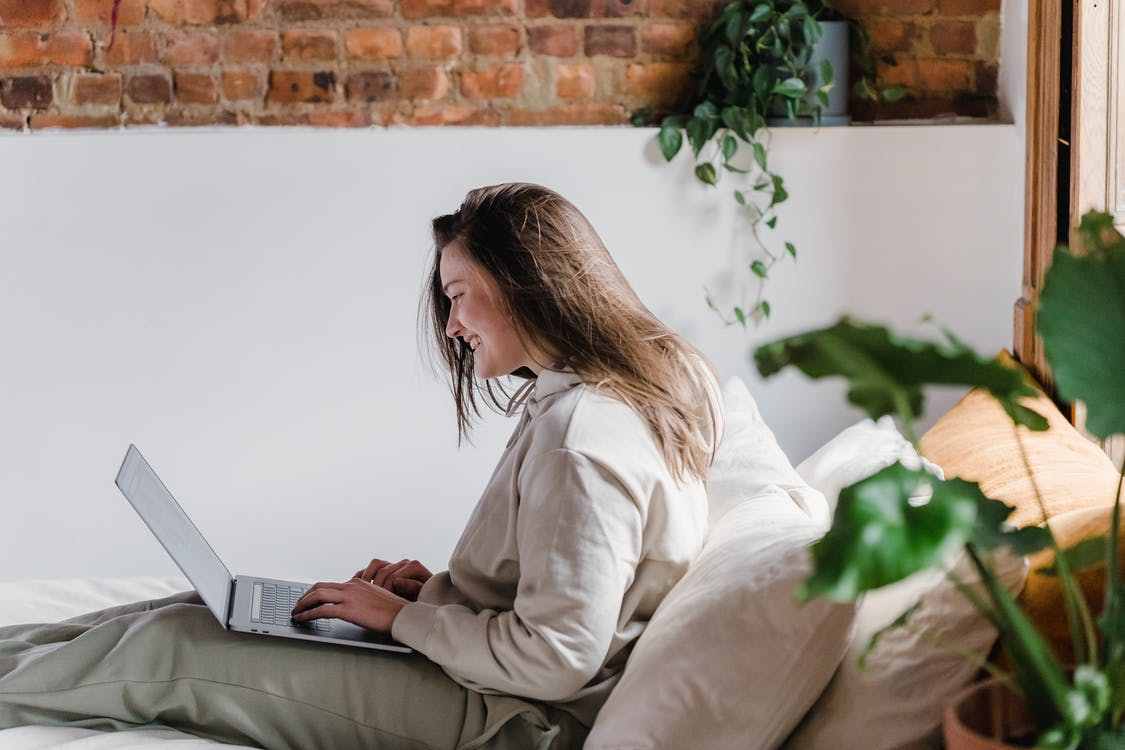 Side view of positive female typing on modern netbook while sitting on comfortable bed near brick wall in room with green potted plants