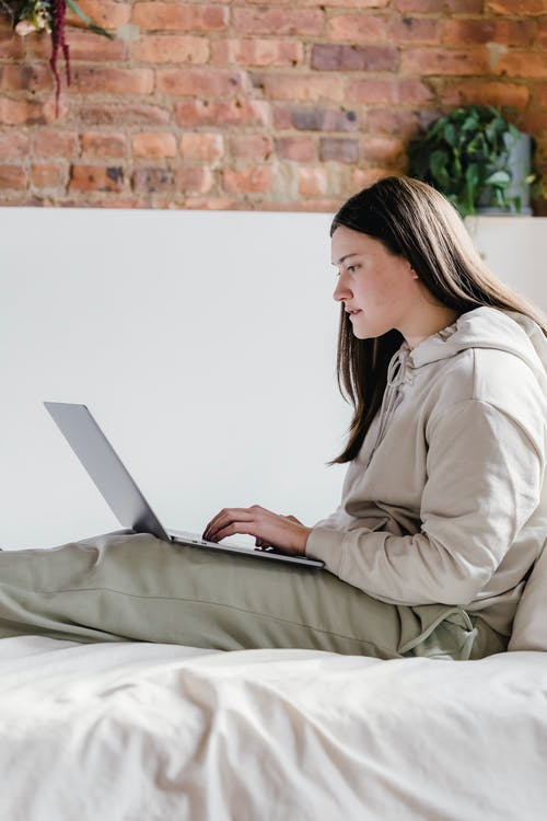 Serious woman browsing laptop in decorated bedroom
