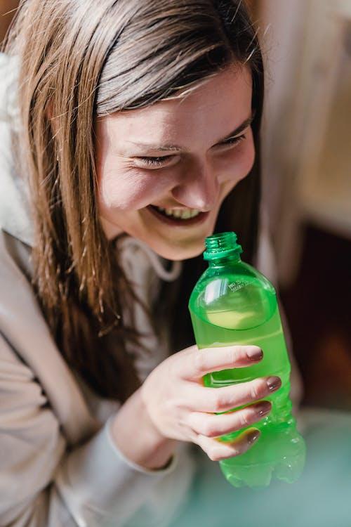 Happy female drinking refreshing beverage from bottle