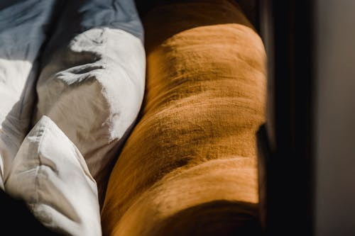 Soft cozy back of brown couch and cushions in white cotton sheets under sunshine from window