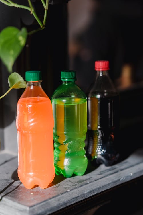 Transparent containers filled with nonalcoholic multicolored liquids of dark coke and orange lemonade and green refreshment placed near home plant on sunlight