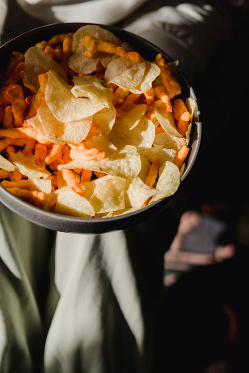 From above of ceramic bowl with delicious chips and snacks against textured surface