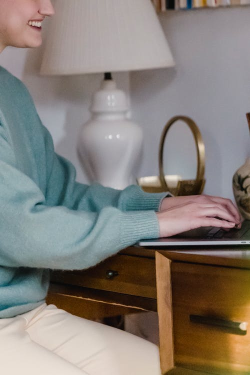 Smiling woman typing on laptop at home