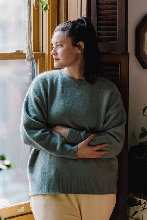 Thoughtful female with folded arms wearing knitted pullover and dreamy contemplating while standing near window