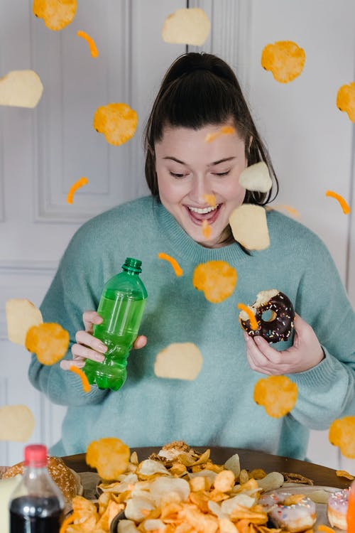 Happy woman with donut and bottle with beverage