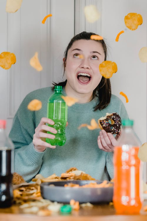 Cheerful young lady with opened mouth holding glazed chocolate bitten donut and bright bottle with fresh drink and surprising at shower of crisps and chips