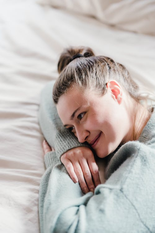 Smiling woman lying on covered bed