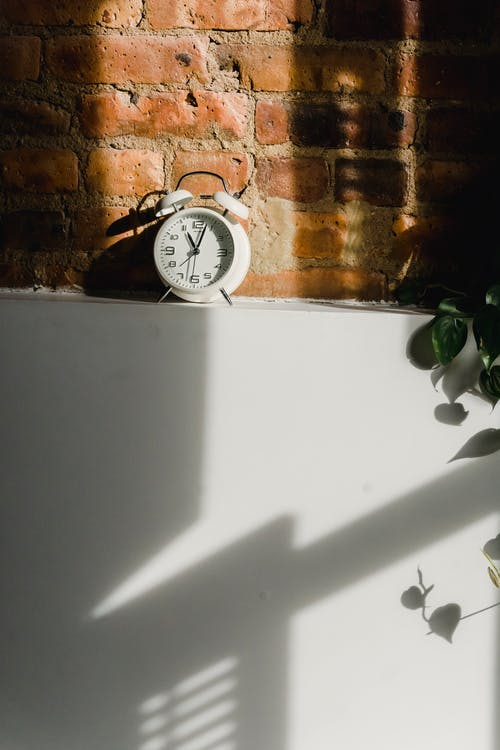 Composition of white alarm clock under sunlight from window illuminating brick wall and fridge with shadows from shutters