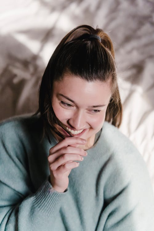 From above of charming female in blue sweater putting hair tip in mouth and smiling while sitting in bedroom under daylight and looking away