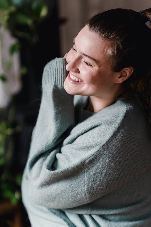 Side view of smiling female wearing warm pullover and looking away thoughtfully while embracing arms