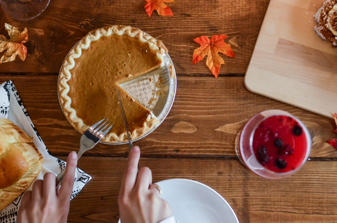 Person Holding Knife and Fork Cutting Slice of Pie on Brown Wooden Table