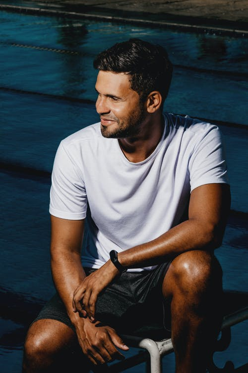 Positive male with beard wearing casual clothes sitting on haunches near swimming pool with clear water on sunny street in summer day