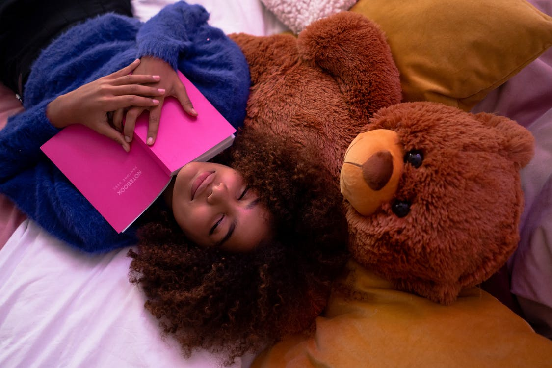 Woman Lying Down on Bed With Her Teddy Bear