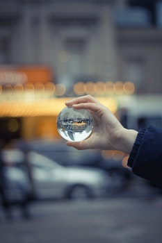 Person Holding Round Glass Ball Macro Shot