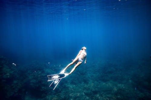 Anonymous lady enjoying snorkeling in blue sea