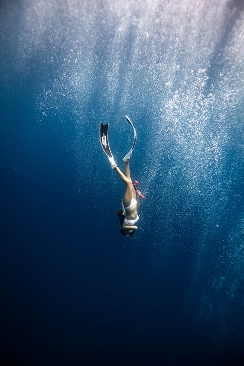 Anonymous female diver swimming under blue ocean in sunlight