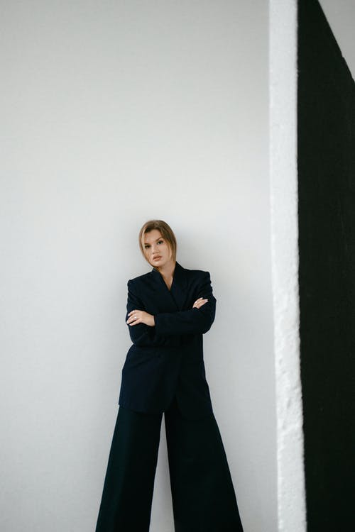 Woman in Black Long Sleeve Shirt and Black Pants Standing Beside White Wall
