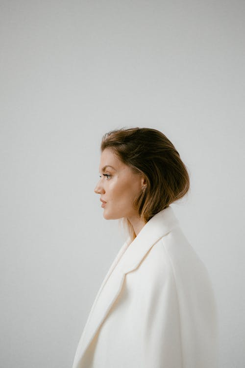 Woman in White Blazer Standing Near White Wall