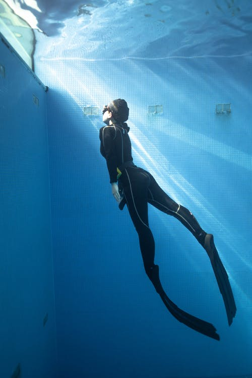 Full body side view of anonymous female in diving suit and flippers with goggles swimming underwater in light blue pool