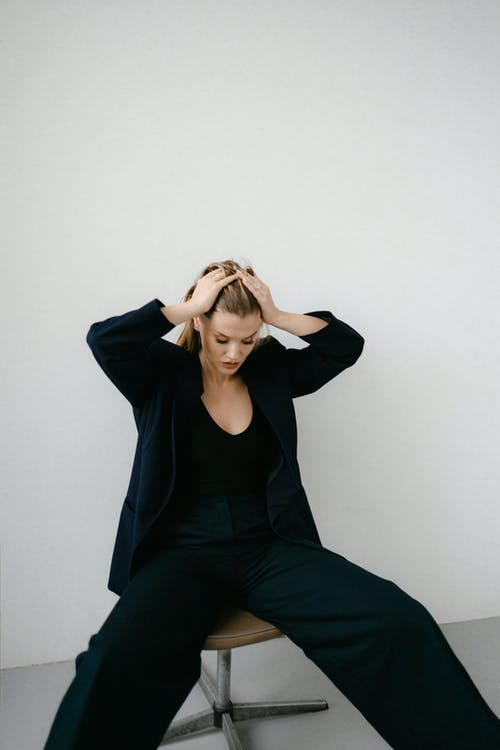 Woman in Black Long Sleeve Shirt and Black Pants Sitting on Floor