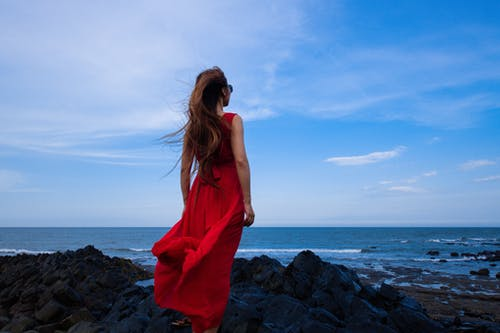 Romantic female in dress standing on rocky coast and looking at ocean