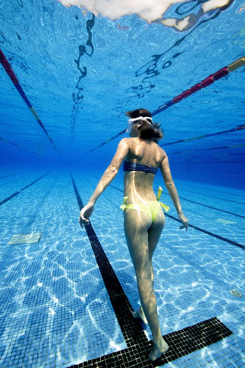 Back view of unrecognizable woman in swimsuit swimming in clean water of pool in daylight