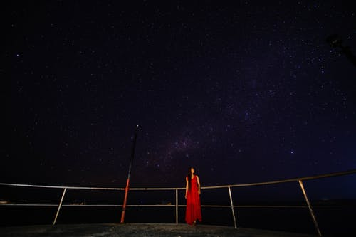 Anonymous woman on viewpoint admiring starry sky at night