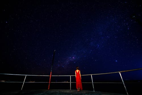 Full body back view of unrecognizable woman in red dress standing on viewpoint with railing while admiring starry dark sky at night