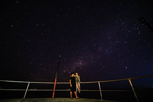 2 Women Standing on Brown Wooden Dock during Night Time